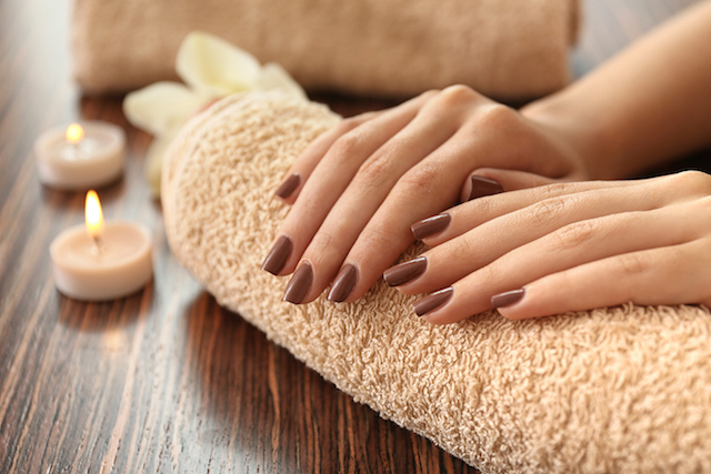 Female hands with brown manicure on towel